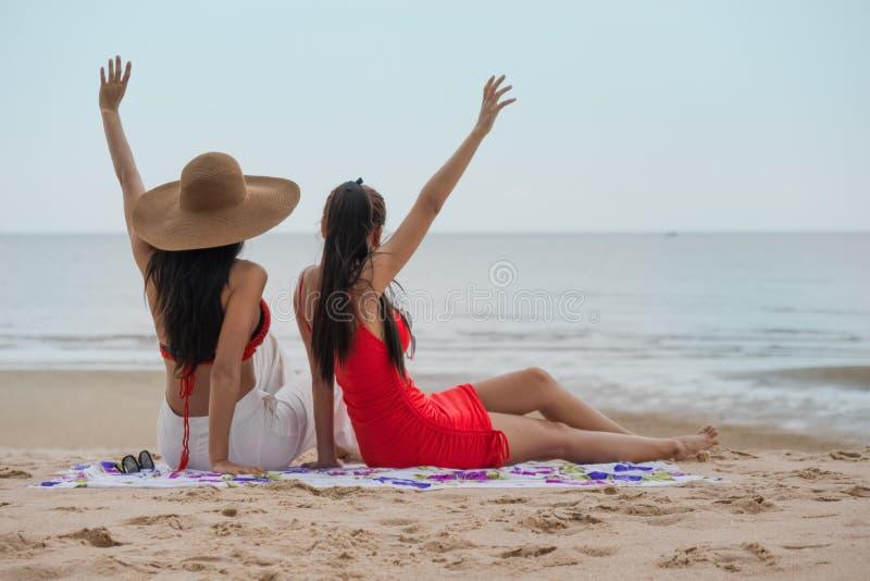一起放松在海滩的女性朋友由海在度假暑假 免版税库存照片
