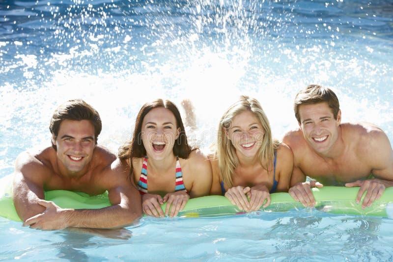 一起放松在游泳池的小组朋友 免版税库存图片