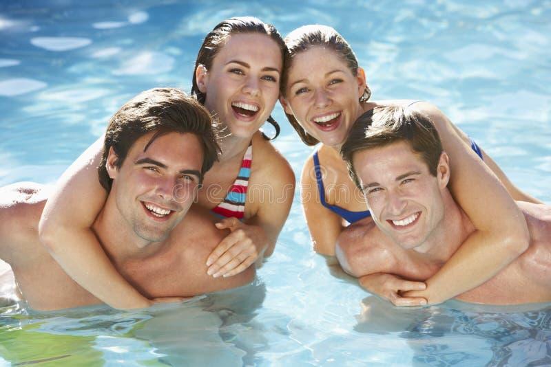 一起放松在游泳池的小组朋友 免版税库存照片