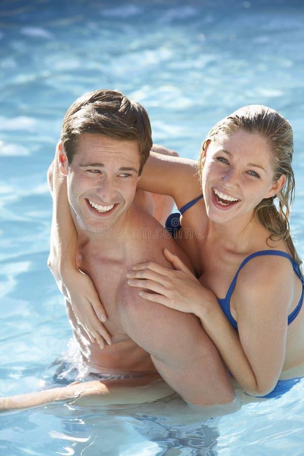 一起放松在游泳池的年轻夫妇 免版税库存照片
