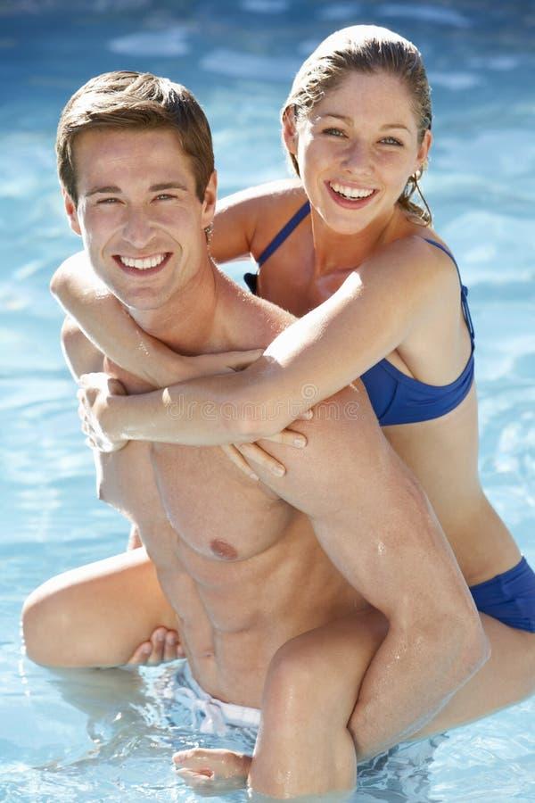 一起放松在游泳池的年轻夫妇 库存照片