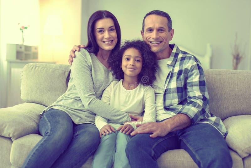 一起放松在长沙发的团结的三口之家 免版税库存照片