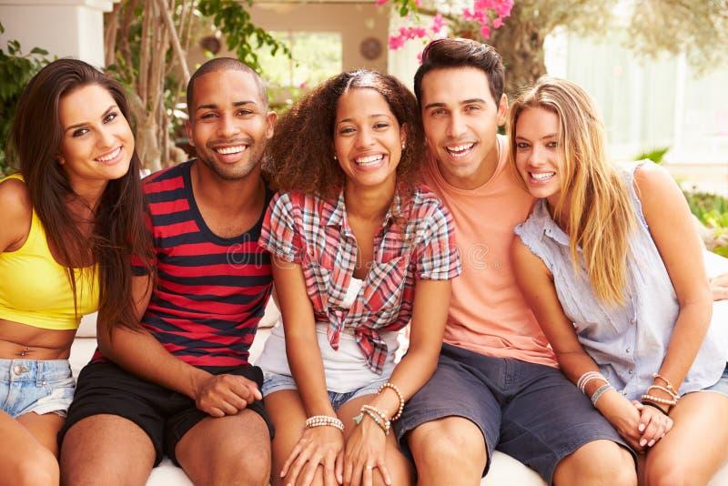 一起放松户外在度假的小组朋友 免版税库存图片