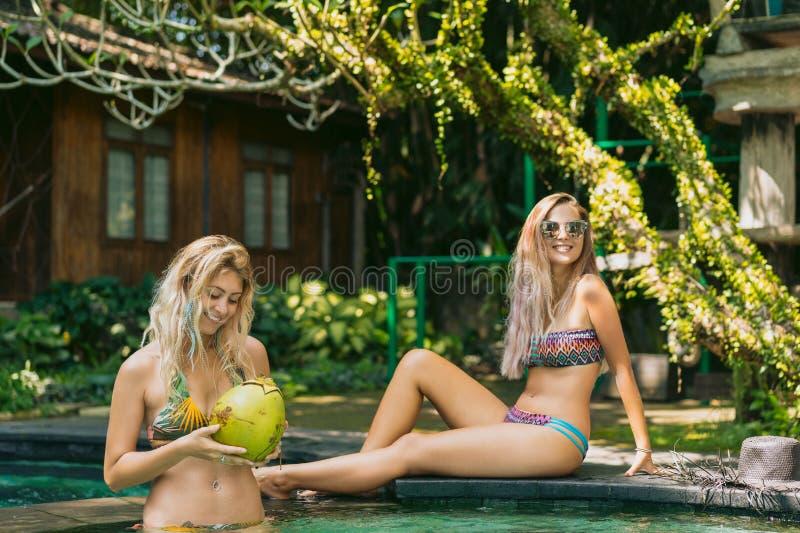一起放松的比基尼泳装的美丽的愉快的年轻女人 免版税库存照片