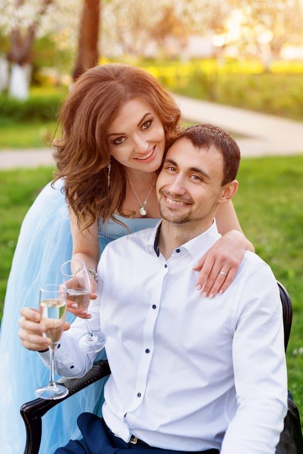 一起新郎和新娘,婚姻夫妇 拥抱年轻的夫妇,饮用的香槟在开花的春天庭院里 爱和 免版税库存照片