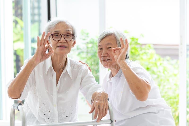 一起显示好标志用的愉快的两名亚裔资深妇女手和手指,优秀年长妇女的标志、朋友或姐妹 免版税库存图片