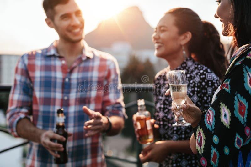 一起朋友在与饮料的屋顶 库存图片