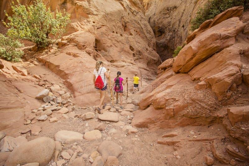 一起步行在砂岩槽孔峡谷的家庭在拱门国家公园附近 库存图片