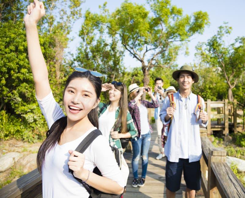 一起步行通过森林的年轻小组 免版税库存照片