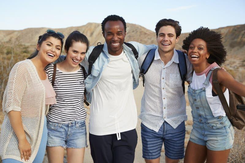 一起步行通过沙漠乡下的年轻朋友画象  免版税库存图片