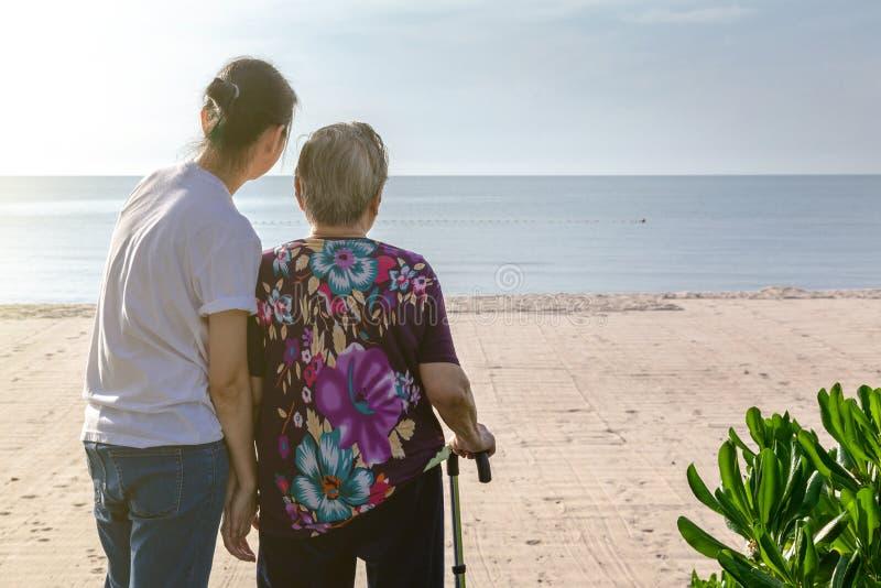 一起母亲和女儿立场在看海的海滩前面 免版税库存图片