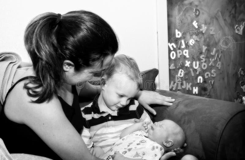 一起母亲&哥哥举行新出生的小兄弟在长沙发 库存图片
