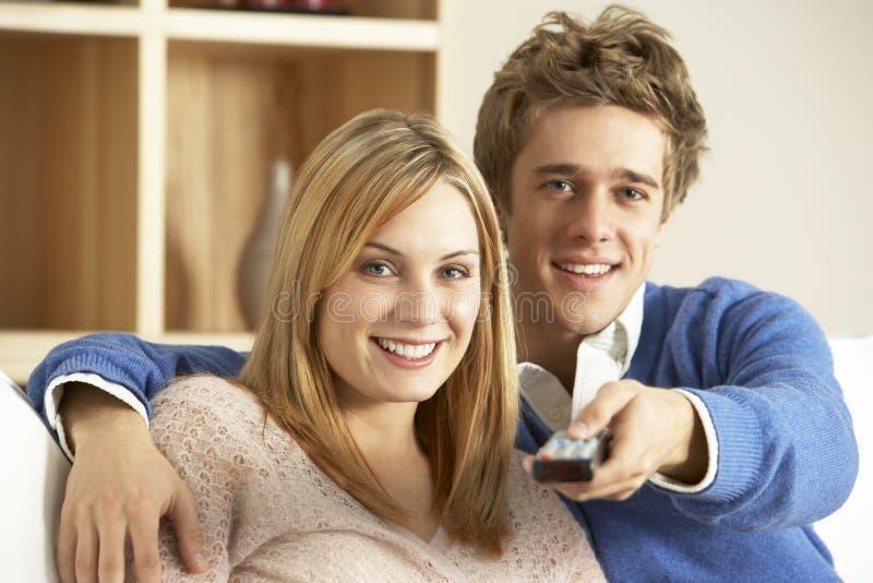 一起注意年轻人的夫妇电视 免版税图库摄影