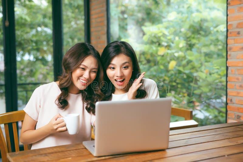 一起浏览互联网的两个多种族年轻女性朋友在膝上型计算机,坐享用一杯咖啡的他们在自助食堂 图库摄影