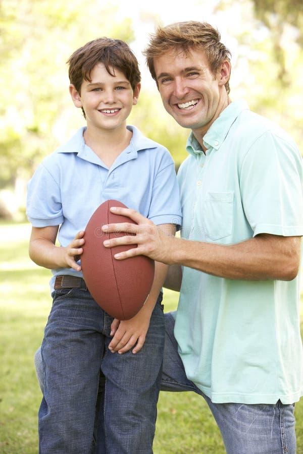 一起演奏儿子的美国父亲橄榄球 图库摄影