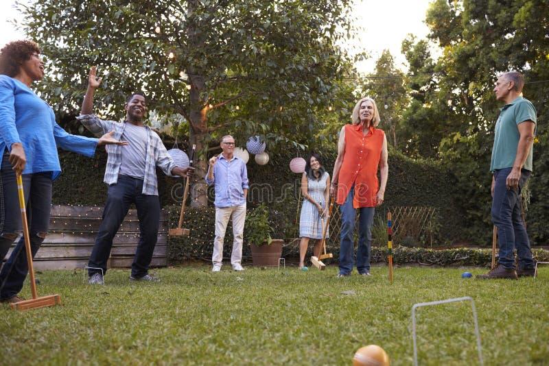 一起演奏槌球的小组成熟朋友在后院 免版税图库摄影