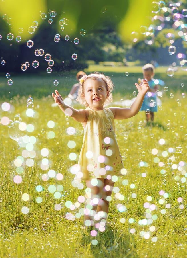 一起演奏肥皂泡的画象两个小女孩的 免版税库存照片