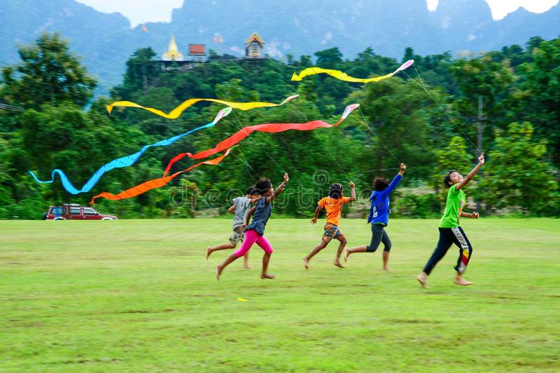 一起演奏风筝的小组农村孩子在领域 免版税库存图片