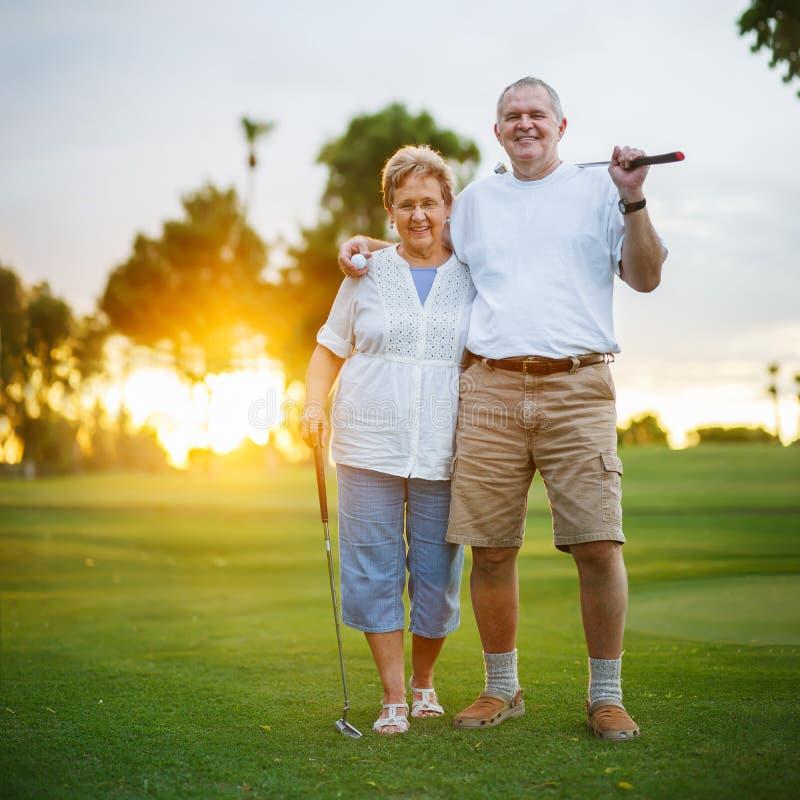 一起演奏高尔夫球画象的资深夫妇 免版税库存照片