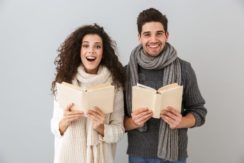 一起激动的男人和妇女看书的图象,被隔绝在灰色backg回合 免版税图库摄影