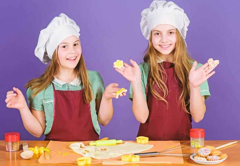 一起烘烤曲奇饼的孩子 孩子围裙和厨师帽子烹调 家庭食谱 r r ?? 库存图片