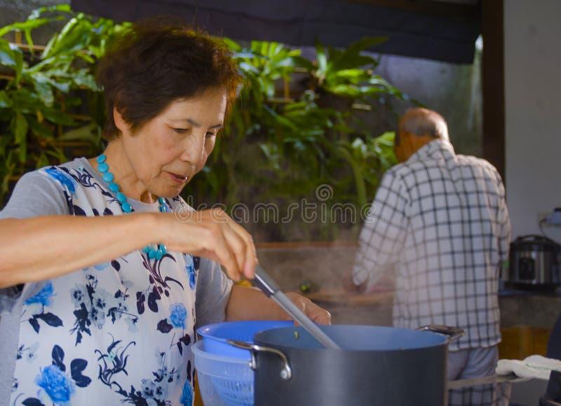 一起烹调厨房的资深愉快和美好的退休的亚洲日本夫妇享用准备膳食在家放松了 免版税库存图片