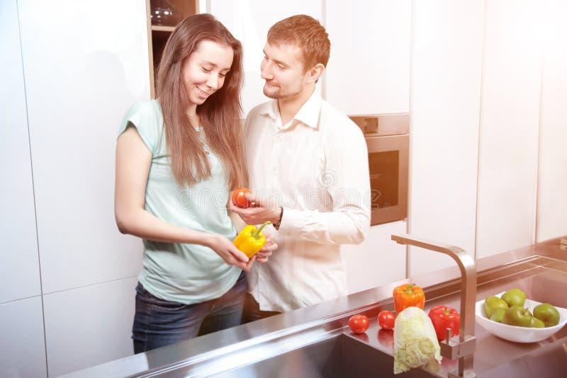 一起烹调在厨房里的愉快的年轻夫妇画象  库存图片