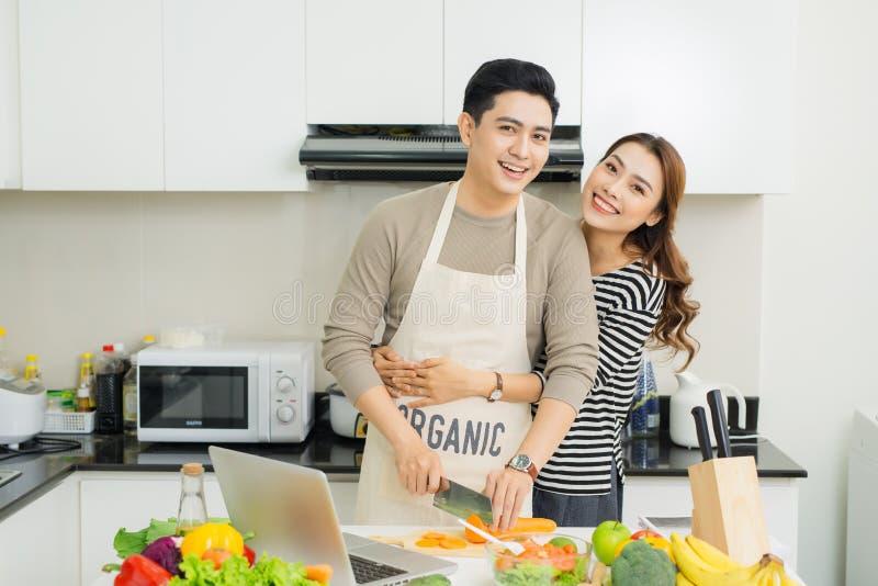 一起烹调在成套工具的愉快的亚洲年轻夫妇画象  库存图片