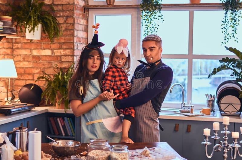 一起烹调在顶楼样式厨房里的妈妈爸爸和小女儿有构成的和帽子在早晨 库存照片