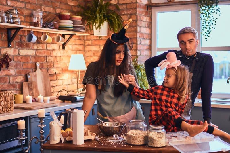 一起烹调在顶楼样式厨房里的妈妈爸爸和小女儿有构成的和帽子在早晨 库存图片