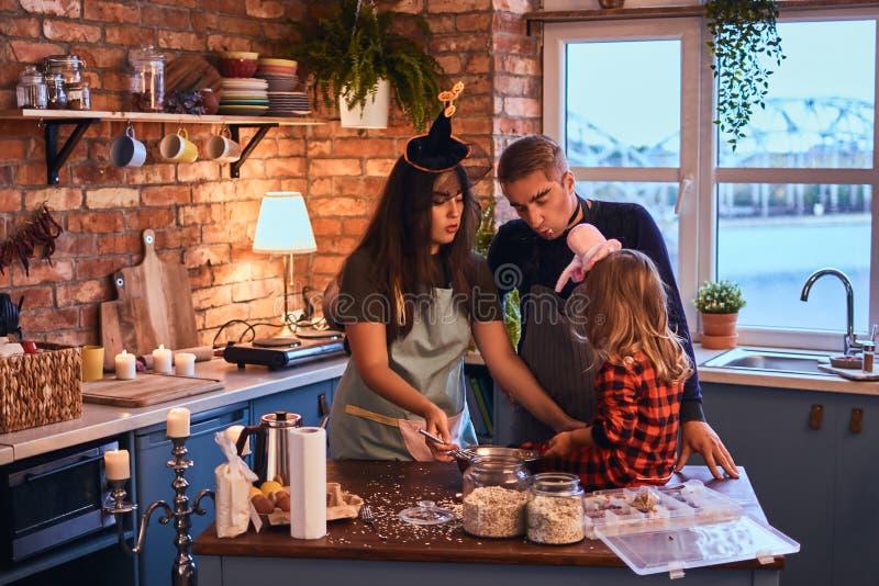 一起烹调在顶楼样式厨房里的妈妈爸爸和小女儿有构成的和帽子在早晨 图库摄影