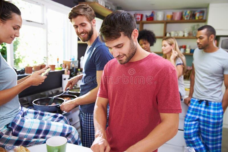 一起烹调早餐的小组朋友在厨房里 库存照片