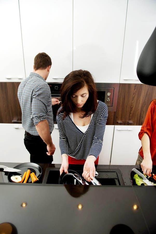 一起烹调膳食的兄弟和姐妹 免版税库存图片