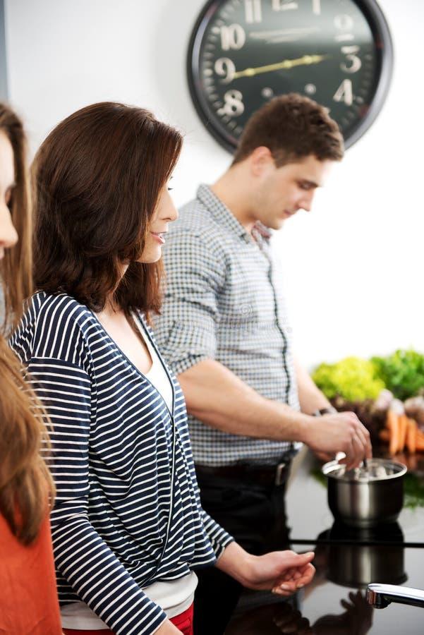 一起烹调膳食的兄弟和姐妹 库存照片
