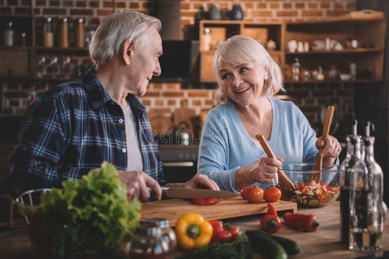 一起烹调菜沙拉的资深夫妇 免版税库存图片
