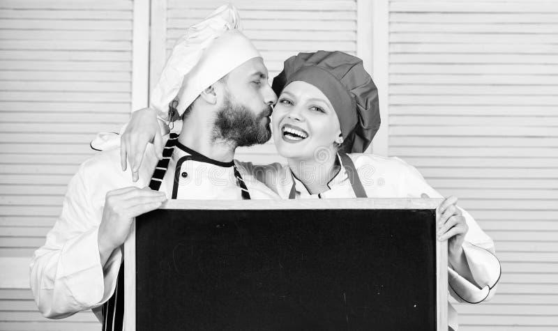 一起烹调食物的男人和妇女厨师 加上广告的黑板 在厨房的可爱的家庭 ?? 免版税库存图片
