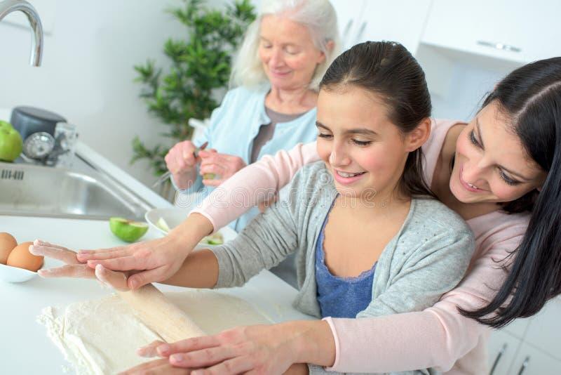 一起烹调画象三世代愉快的美丽的妇女 免版税库存照片