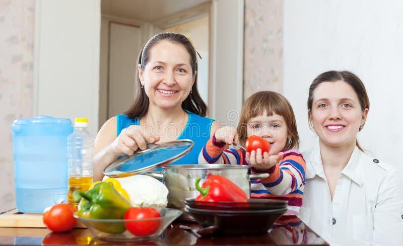 一起烹调素食者午餐的愉快的家庭 免版税库存照片