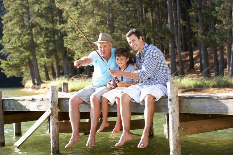 一起父亲、儿子和孙子捕鱼 库存图片