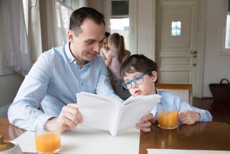 一起父亲和儿子看书在餐厅 免版税库存照片