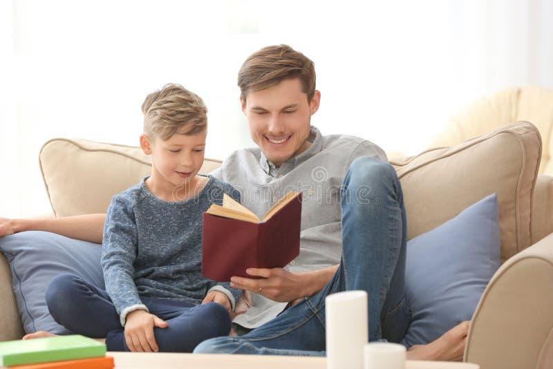 一起父亲和在家他的儿子看书 免版税库存图片