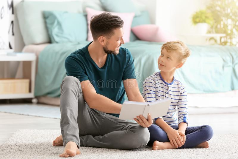 一起父亲和在家他的儿子看书 库存图片
