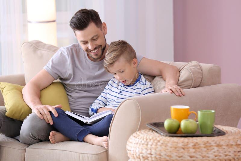 一起父亲和在家他的儿子看书 免版税库存照片