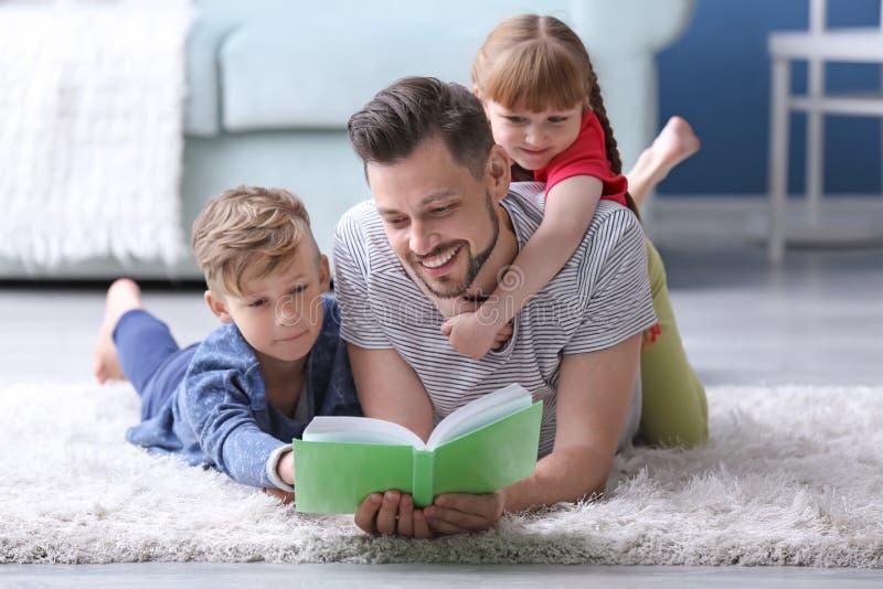 一起父亲和在家他的儿童看书 库存图片