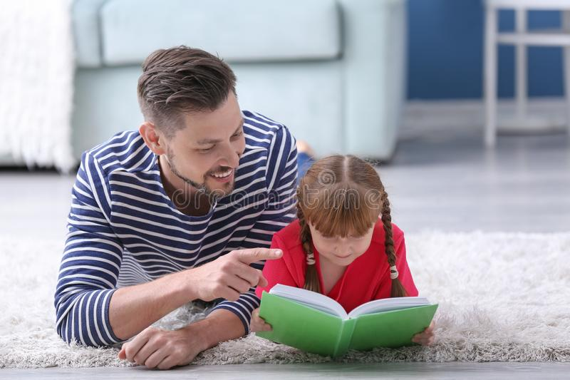 一起父亲和在家他的女儿看书 库存照片
