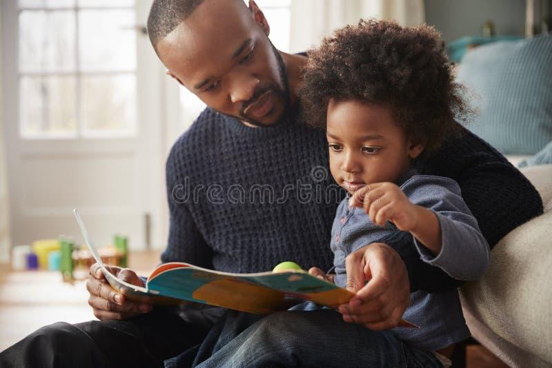 一起父亲和在家年轻儿子阅读书 库存照片