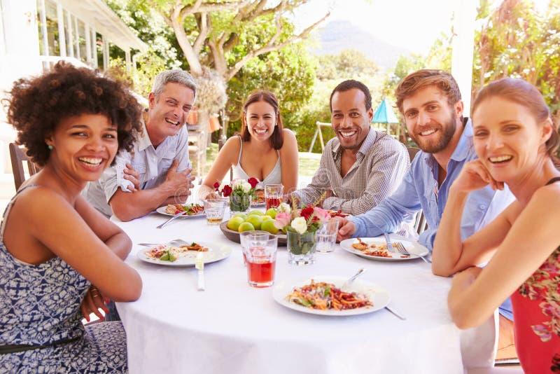 一起用餐在一张桌上的朋友在庭院里 免版税库存图片