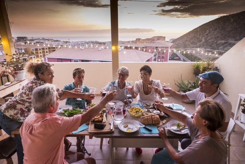 一起用餐小组的朋友和的父母在家和使叮当响的玻璃用饮料 大家微笑和有乐趣庆祝 免版税库存图片