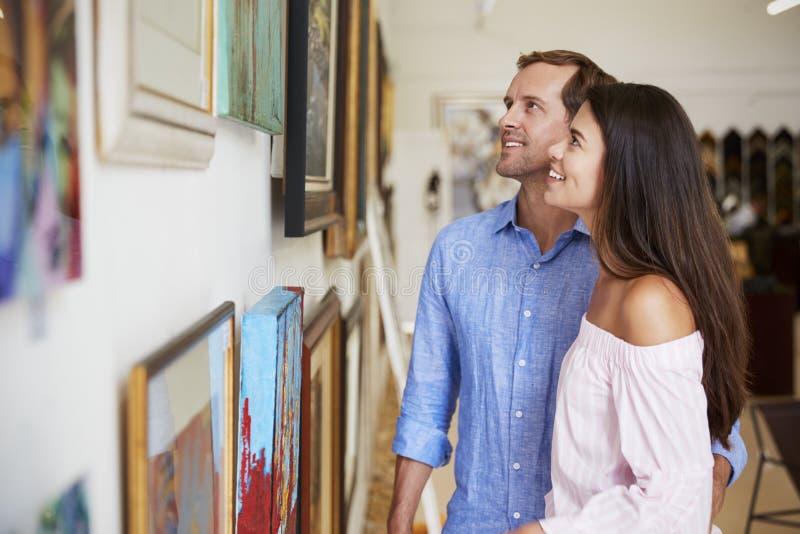 一起看在美术画廊的夫妇绘画 免版税库存照片