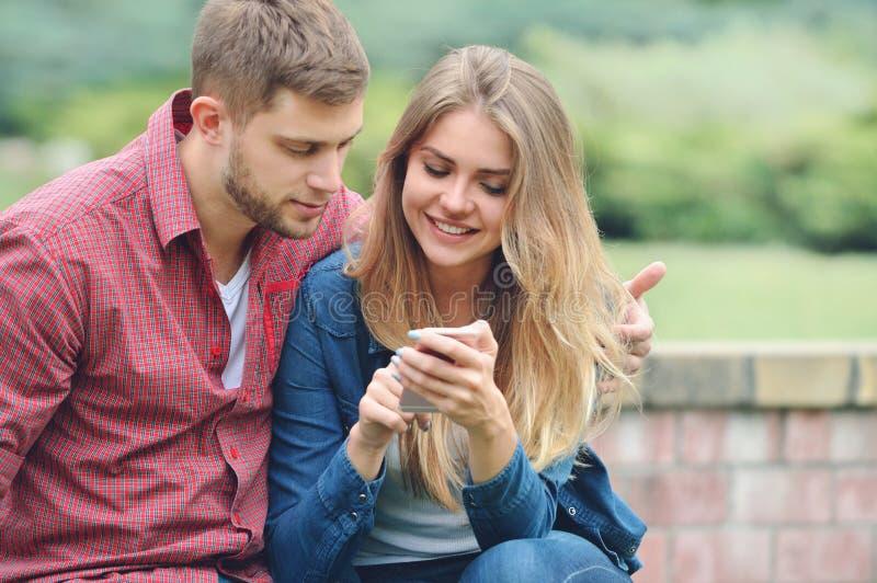 一起看智能手机的年轻夫妇在一条长凳在公园 库存照片